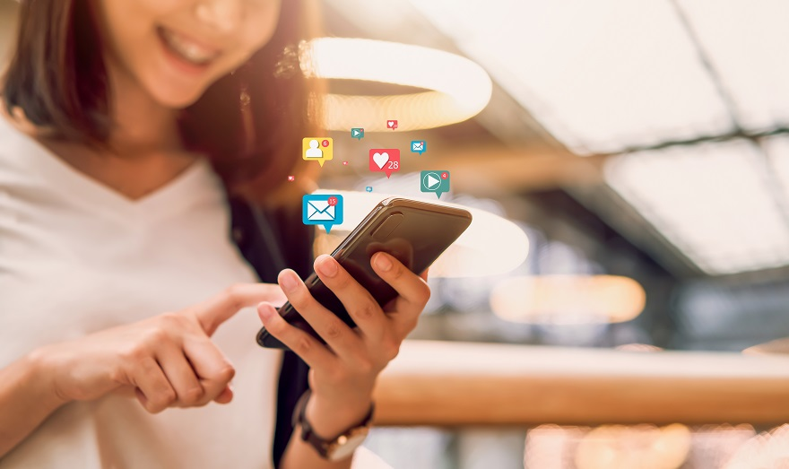 Social media and digital online concept, smiling Asian woman using smartphone and show technology icon.